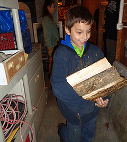Young boy helping carry wood